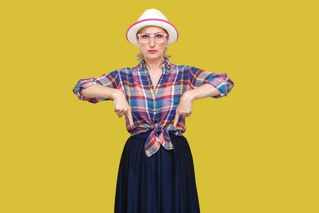 Здесь и прямо сейчас. портрет серьезной современной стильной зрелой женщины в повседневном стиле с шляпой и очками, стоящими и указывающими вниз и смотрящими на камеру. студия выстрел, изолированные на желтом фоне.
