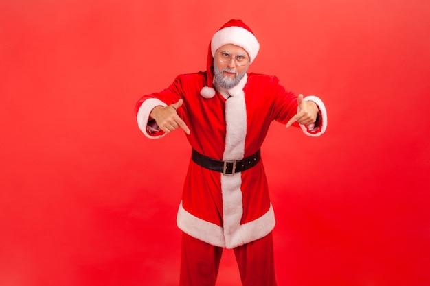 ここと今。サンタクロースが立ってカメラを見て、下を向いています。
