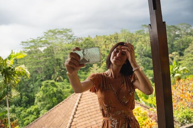 나 여기있어. 섬에서 이국적인 자연을 즐기는 쾌활한 소녀, 그녀의 가제트로 사진 촬영