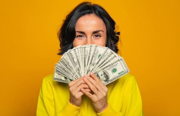 これが私の給料です!黄色いパーカーを着た少女が、目で笑って、手に多額のお金の後ろに顔を隠している。