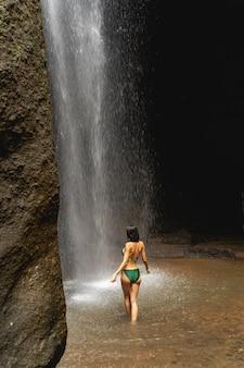 여기있어. 바위 근처에서 수영을 하는 동안 폭포를 바라보며 기뻐하는 소녀