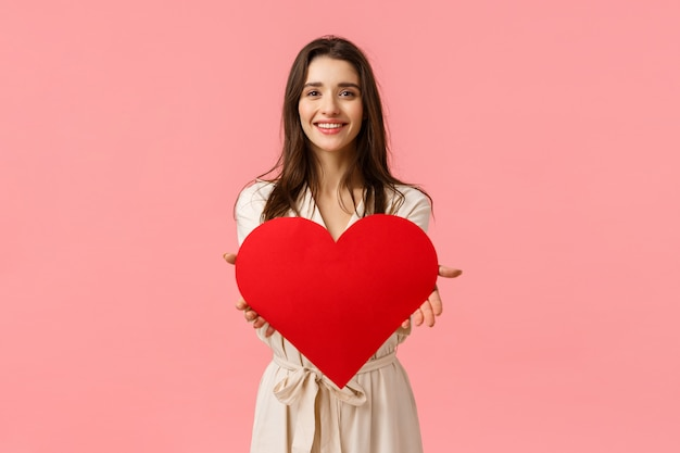 Here my love to you. charming tender and alluring, romantic young woman giving big heart card, smiling delighted, express her affection and admiration, standing pink wall