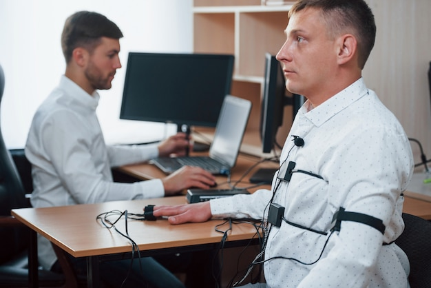 Здесь никто никого не осуждает, не волнуйтесь. подозрительный мужчина проходит детектор лжи в офисе. задавать вопросы. проверка на полиграфе