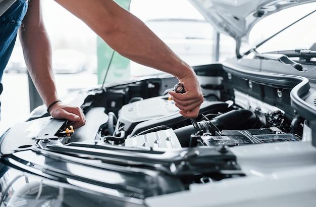 Вот так. процесс ремонта автомобиля после аварии. человек, работающий с двигателем под капотом.