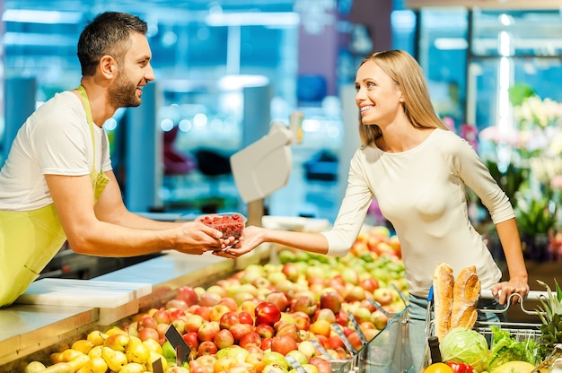 Here you go! side view of young cashier giving raspberries to female customer while standing in food store