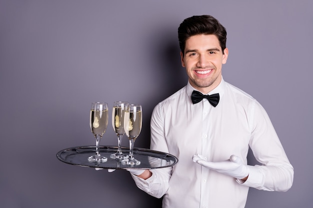 Here your order. positive cheerful waiter bring client guest alcohol wine standing on tray show point hand wear white shirt uniform gloves isolated over grey color wall