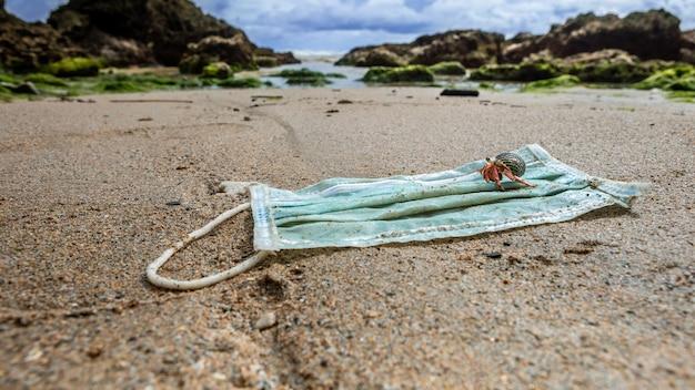海の水で使用済みの医療用マスクからゴミの上を歩くヤドカリ。汚染や海洋の性質の汚染などの悪い結果。環境および海岸の汚染covid19