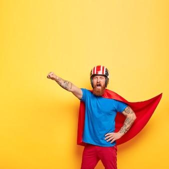 Personaggio maschile eroico vestito con un costume da supereroe, grida con coraggio che sono pronto a volare, fa un gesto di volo