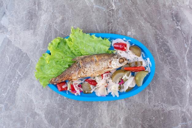 청어와 파란색 접시에 절인 야채입니다.