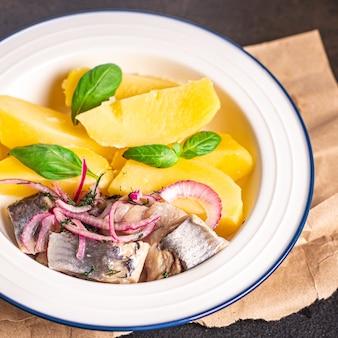 Селедка и картофель вторые блюда маринованная рыба лук свежий готовый к употреблению закуска на столе