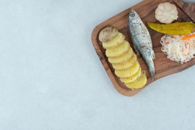 ニシン、茹でたジャガイモ、ミックスピクルスを木の板に。