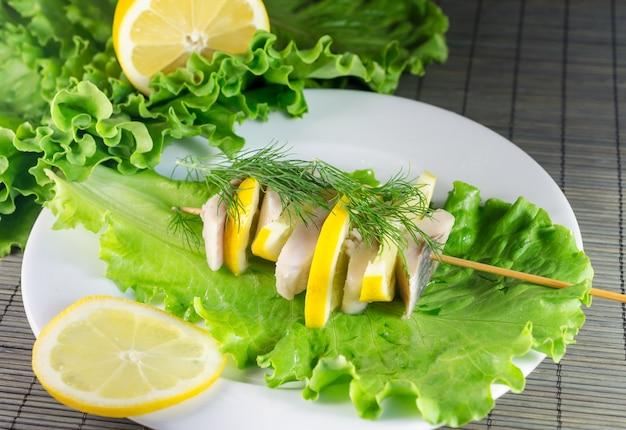 Herring filet garnished with lettuce and lemon