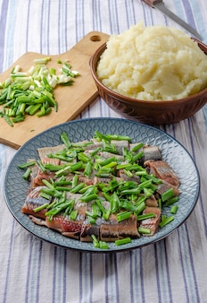 Herring fillet sliced green onions with mashed potatoes  on a blue plate. light wood background.