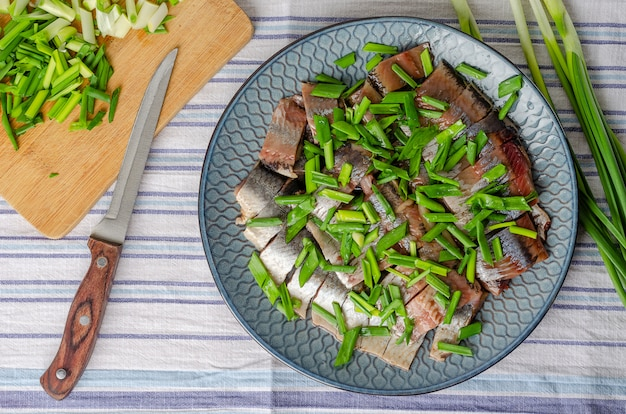 Herring fillet sliced into chunks with green onions on a blue plate. light wood background.