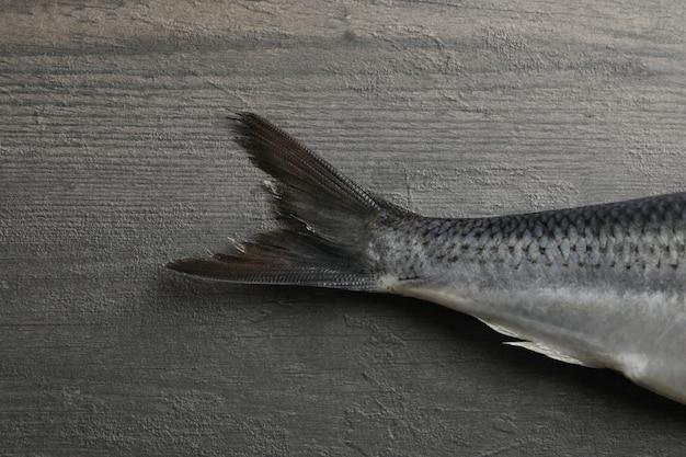 Хвост рыбы сельдь на сером деревянном