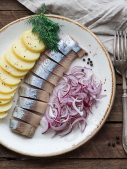 Herring fish with potatoes slices and red onion  on the table with fork and kitchen towel.
