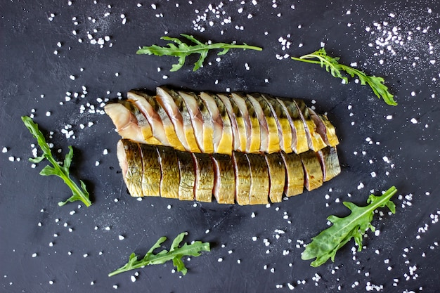 Herring and mackerel on a dark surface with onions and arugula