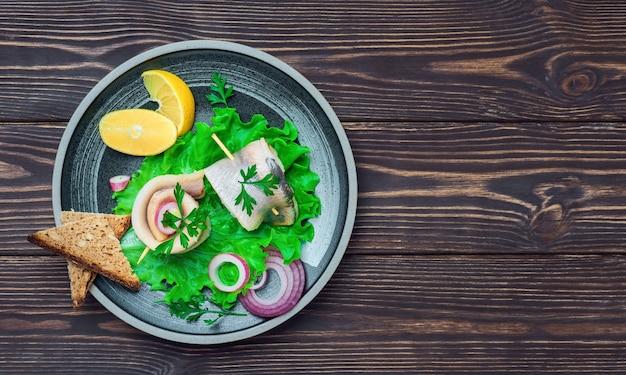 Рулет из селедки на шпажке на листе салата с петрушкой, луком и долькой лимона, вид сверху. сэндвичи разложены на тарелке на темном деревянном фоне с местом для текста. быстрое питание или закуски.
