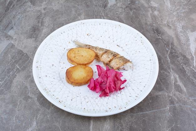 Рулетики из сельди, картофель и краснокочанная капуста на белой тарелке.
