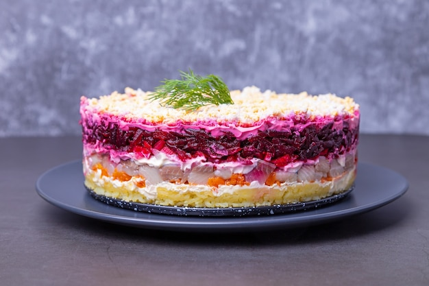 Herring salad under a fur coat. traditional russian multilayered salad from herring, beets, potatoes, carrots and eggs. close-up, grey background.
