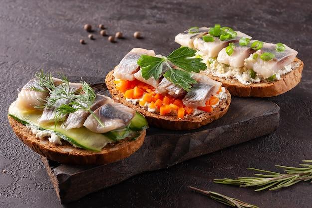 Бутерброды с селедкой на деревянной доске на коричневом камне