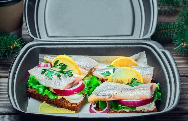 Бутерброды с селедкой с ржаным хлебом, петрушкой и лимоном в контейнере для фастфуда, традиционный датский сморреброд. крупный план