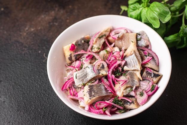 Селедка кусочки лука маринованная соленая рыба морепродукты свежие готовые закуски на столе