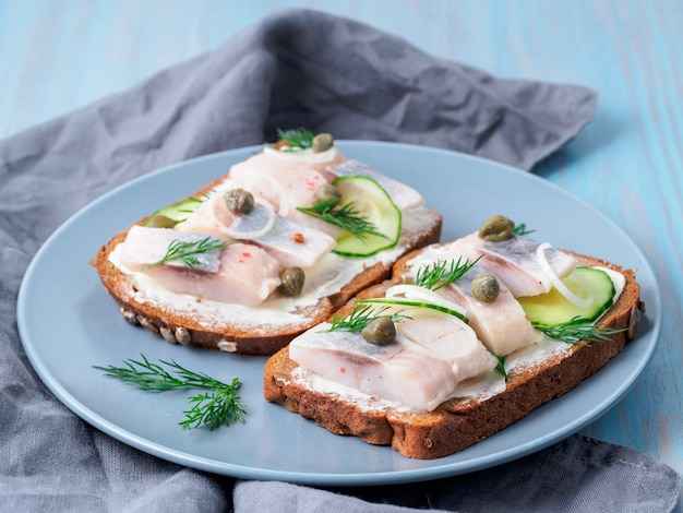 Herring smorrebrod - traditional danish sandwiches. black rye bread with herring on dark background