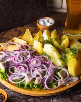 ゆでたジャガイモバターレッドオニオンディルの塩とビールのグラスとニシン