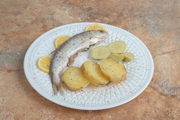 Aringhe con patate bollite sulla zolla bianca