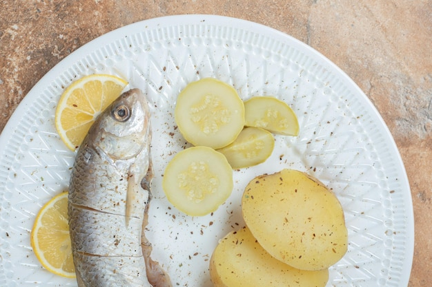 Herring with boiled potatoes on white plate