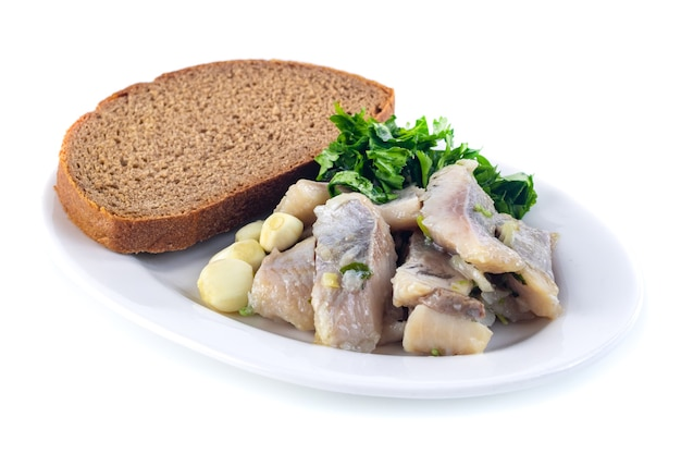 Селедка с черным хлебом, луком, чесноком и петрушкой на белой тарелке, здоровое питание