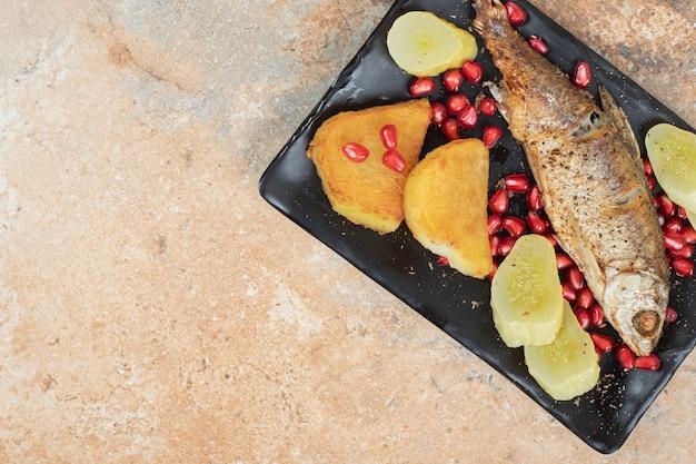Селедка с жареным картофелем и солеными огурцами на черной тарелке
