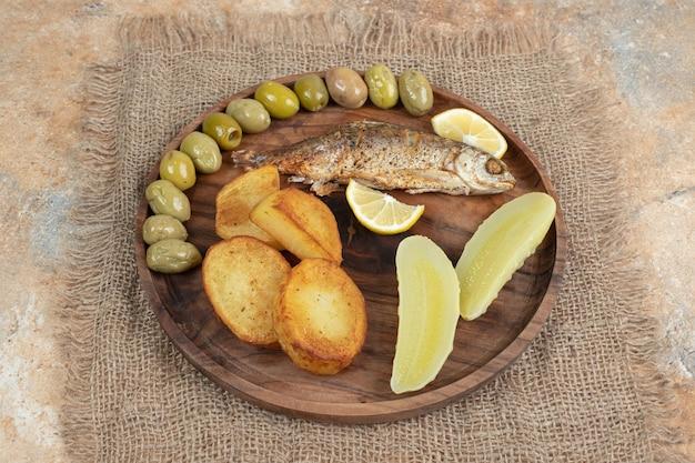 Селедка с жареным картофелем и солеными огурцами на деревянной тарелке