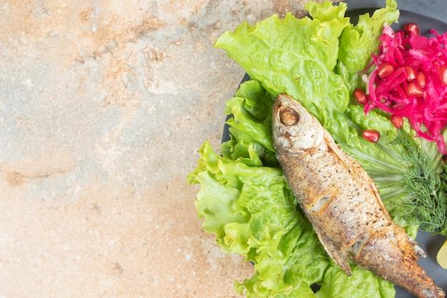 Селедка с салатом и красной капустой на деревянной тарелке.