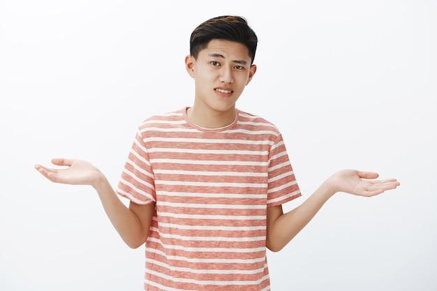 Esitante giovane ragazzo asiatico attraente con i capelli scuri che scrolla le spalle allargando le mani lateralmente come fare una scelta difficile o una decisione essendo incapace e dubbioso, non può scegliere