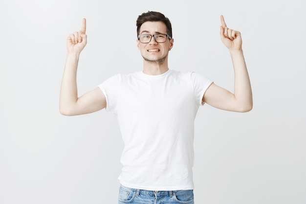 Hesitant awkward guy in glasses pointing fingers up and looking concerned