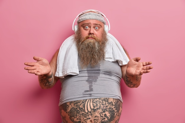 Hesitant bearded adult man spreads palms and looks confused, has regular workout for weight loss, listens music in headphones, wears headband and undersized t shirt, tattooed belly sticking out