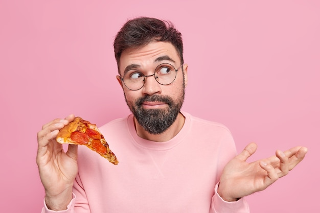 Hesitant bearded young man shrugs shoulders holds tasty pizza being unaware looks clueless away dressed in casual clothes