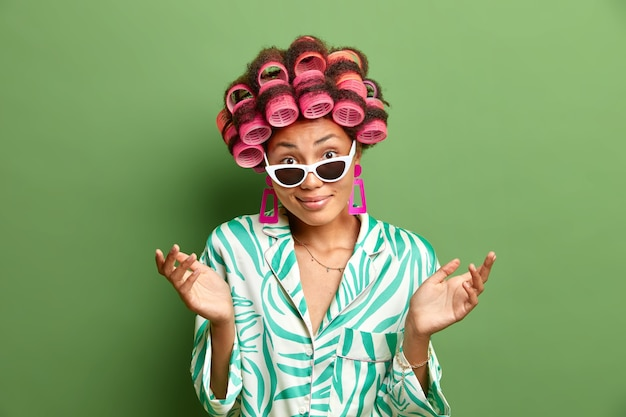 Hesitant clueless dark skinned woman spreads palms and looks doubtful  wears sunglasses hair rollers dressing gown cannot make up her mind poses against green wall. domestic style
