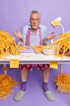 躊躇する無知な老人が手のひらを広げて、紫色の壁に隔離されたプロのアナリストであるカット紙に囲まれた財務報告を行う方法を知らないと感じています