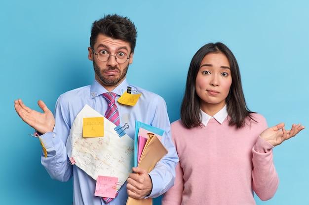 Нерешительные коллеги пожимают плечами и сотрудничают для выполнения общей задачи. незнающие ученики не знают, как подготовить проект к успешной работе