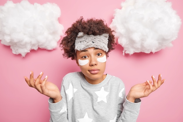 Hesitant curly haired woman spreads palms feels doubt dressed in nightwear applies collagen patches under eyes to remove dark circles wears nightwear isolated over pink wall with clouds above