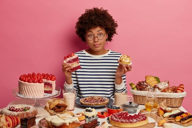 주저하는 어두운 피부의 곱슬 머리 여자는 선택할 케이크 조각을 의심하고 정크 푸드를 먹고 싶은 유혹을 느끼며 분홍색 배경에 디저트가있는 큰 축제 테이블에서 포즈를 취합니다.