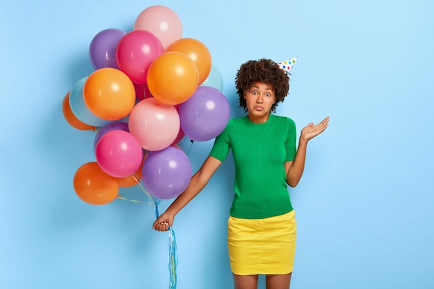 Hesitant dark skinned woman feels confused, raises palm, has curly afro hairstyle, dressed in green t shirt and yellow skirt, holds colorful multicolored balloons hesitates where to celebrate birthday