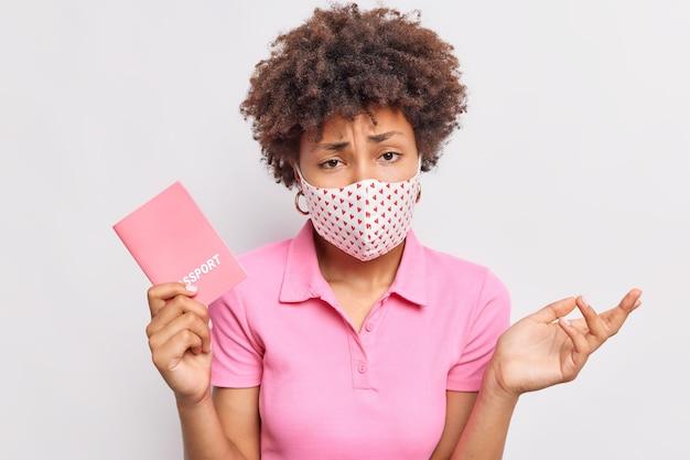 躊躇する不快な巻き毛のアフロアメリカ人女性は無知な表情で見えますコロナウイルスのパンデミックの間に飛行する予定の保護マスクを着用しますカジュアルなtシャツに身を包んだパスポートを保持します
