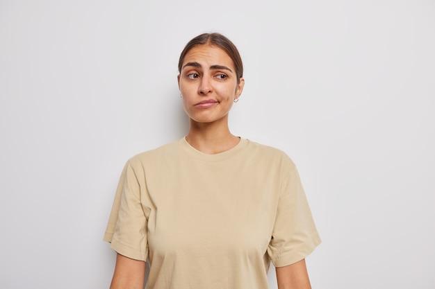 Нерешительная недовольная женщина поджимает губы, сомневается, что выражение недовольства думает о чем-то, одетом в бежевую футболку, изолированном над белой стеной студии