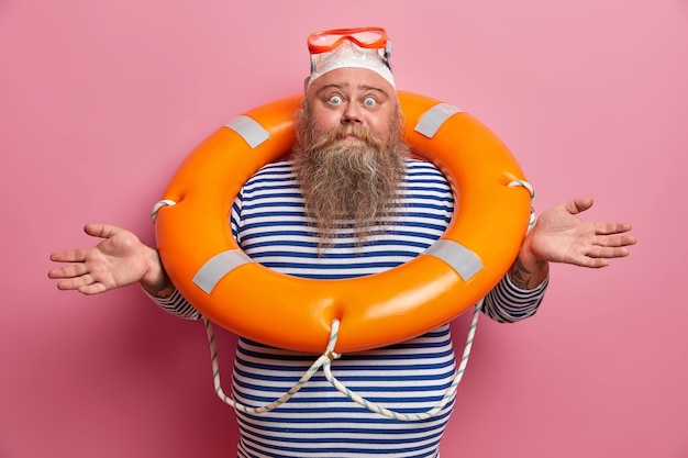 Hesitant doubtful bearded man spreads hands sideways, feels confused, wears swimming hat, goggles and sailor t shirt, poses with inflated lifebuouy isolated on pink wall. overweight lifesaver at beach