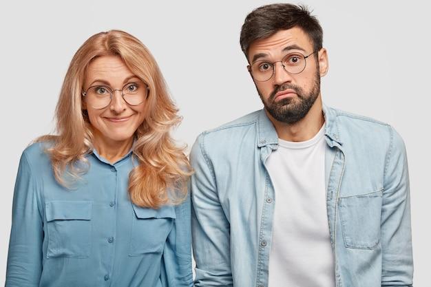 躊躇している疑わしい男女の同僚、いつ仕事を始めたらいいのかわからない、隣同士に立っている、無知な表情をしている
