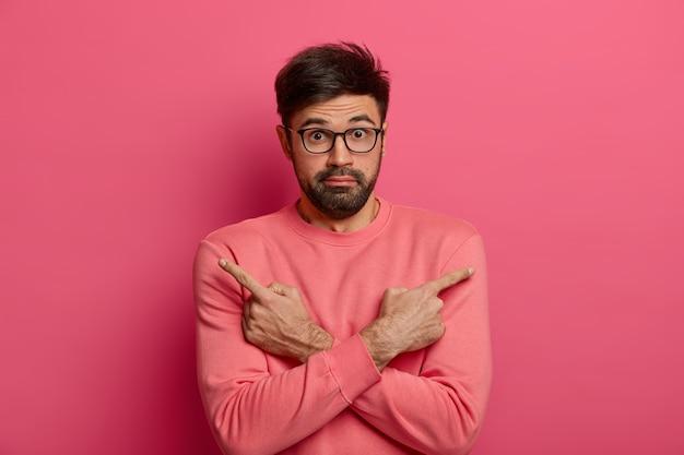 L'uomo barbuto esitante e imbarazzato indica di lato, tiene le braccia incrociate sul corpo, sceglie l'oggetto necessario, ha un'espressione dubbiosa e sorpresa, vestito con un maglione rosa brillante. due opzioni o varianti